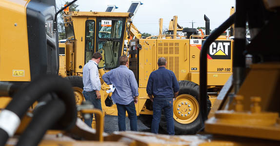Customers inspecting Caterpillar heavy equipment at a Ritchie Bros. auction site