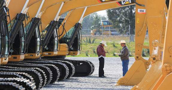 Potential buyers inspecting excavators in Mexico