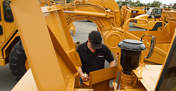 Inspecting heavy equipment for sale at Ritchie Bros.